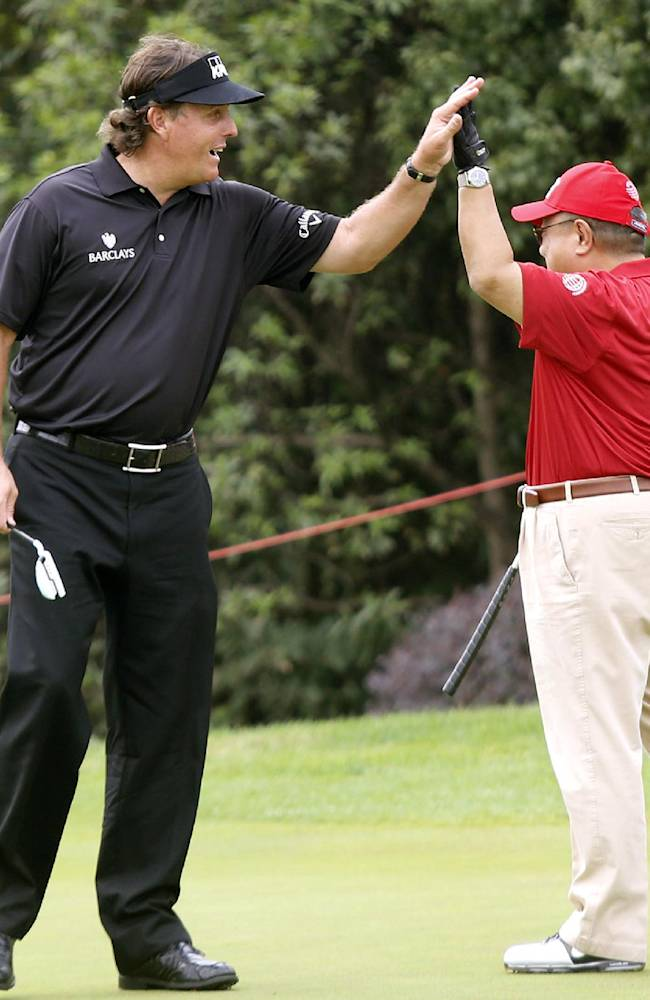 Phil Mickelson of the United States, left, and an amateur player celebrate at the 5th hole during the Pro-Am event of the HSBC Champions golf tournament, which begins on Thursday, at the Sheshan International Golf Club in Shanghai, China, Wednesday, Oct. 30, 2013. (AP Photo)