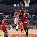 Chicago Bulls guard D.J. Augustin, center, flies past Atlanta Hawks' Louis Williams, left, and Paul Millsap (4) during the first half of an NBA basketball game Tuesday, Feb. 11, 2014, in Chicago The Associated Press