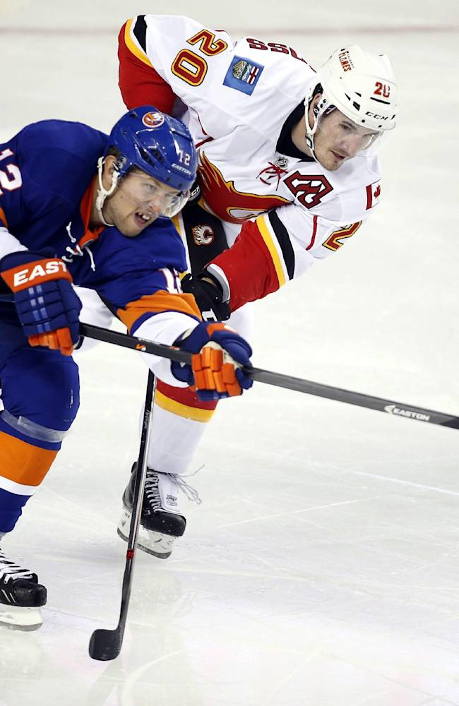 New York Islanders' Josh Bailey, left, gets the puck away from Calgary Flames' Curtis Glencross during the second period of a split-squad preseason NHL hockey game in Calgary, Alberta, Tuesday, Sept. 17, 2013
