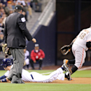San Diego Padres' Chris Denorfia, bottom, slides in safely on a triple as San Francisco Giants third baseman Pablo Sandoval, right, fields a wide throw from right center in the first inning of a baseball game on Friday, April 18, 2014, in San Diego The As