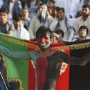 An Afghan spectator, with his face painted with the colours of Afghanistan's national flag, watches a friendly soccer match between Afghanistan and Pakistan in Kabul August 20, 2013. REUTERS/Omar Sobhani