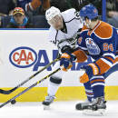 Los Angeles Kings' Trevor Lewis (22) and Edmonton Oilers' Oscar Klefbom (84) battle for the puck during first period of an NHL hockey game in Edmonton, Alberta, Tuesday, March 3, 2015. (AP Photo/The Canadian Press, Jason Franson)
