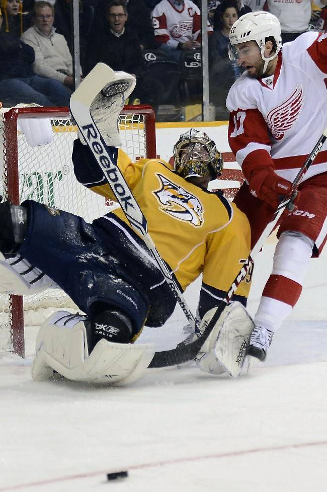 Detroit Red Wings forward Patrick Eaves (17) collides with Nashville Predators goalie Marek Mazanec (39), of the Czech Republic, after his shot was blocked by Mazanec in the first period of an NHL hockey game on Monday, Dec. 30, 2013, in Nashville, Tenn