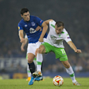 Wolfsburg's Ivica Olic, right, fights for the ball against Everton's Gareth Barry during their Europa League Group H soccer match at Goodison Park Stadium, Liverpool, England, Thursday Sept. 18, 2014