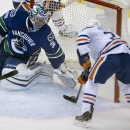 Edmonton Oilers center Mark Arcobello, right, puts the puck past Vancouver Canucks goaltender Ryan Miller (30) during the first period of an NHL hockey game in Vancouver, British Columbia, Saturday, Oct. 11, 2014 The Associated Press