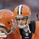 Cleveland Browns quarterback Brian Hoyer talks with Johnny Manziel on the bench in the fourth quarter of an NFL football game against the Cincinnati Bengals, Sunday, Dec. 14, 2014, in Cleveland The Associated Press