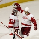 Detroit Red Wings goalie Jimmy Howard, left, celebrates with Jakub Kindl after the Red Wings defeated the Chicago Blackhawks 4-1 IN Game 2 of the NHL hockey Stanley Cup playoffs Western Conference semifinals in Chicago, Saturday, May 18, 2013. (AP Photo/Nam Y. Huh)