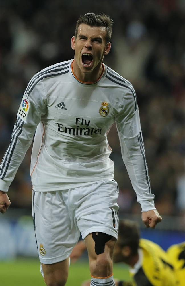 Real's Gareth Bale celebrates after scoring during a Spanish La Liga soccer match between Real Madrid and Sevilla at the Santiago Bernabeu stadium in Madrid, Spain, Wednesday Oct. 30, 2013