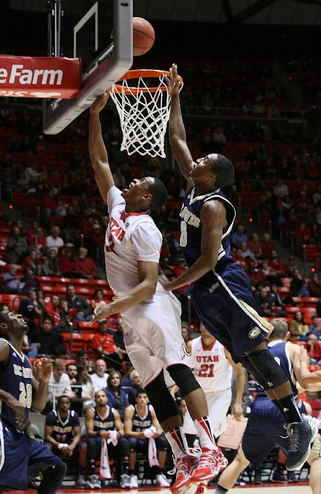 Utah's Princeton Onwas (3) drives for a layup past the defense of UC Davis guard Lemar Brynton during the first half of an NCAA college basketball game Friday, Nov. 15, 2013, in Salt Lake City