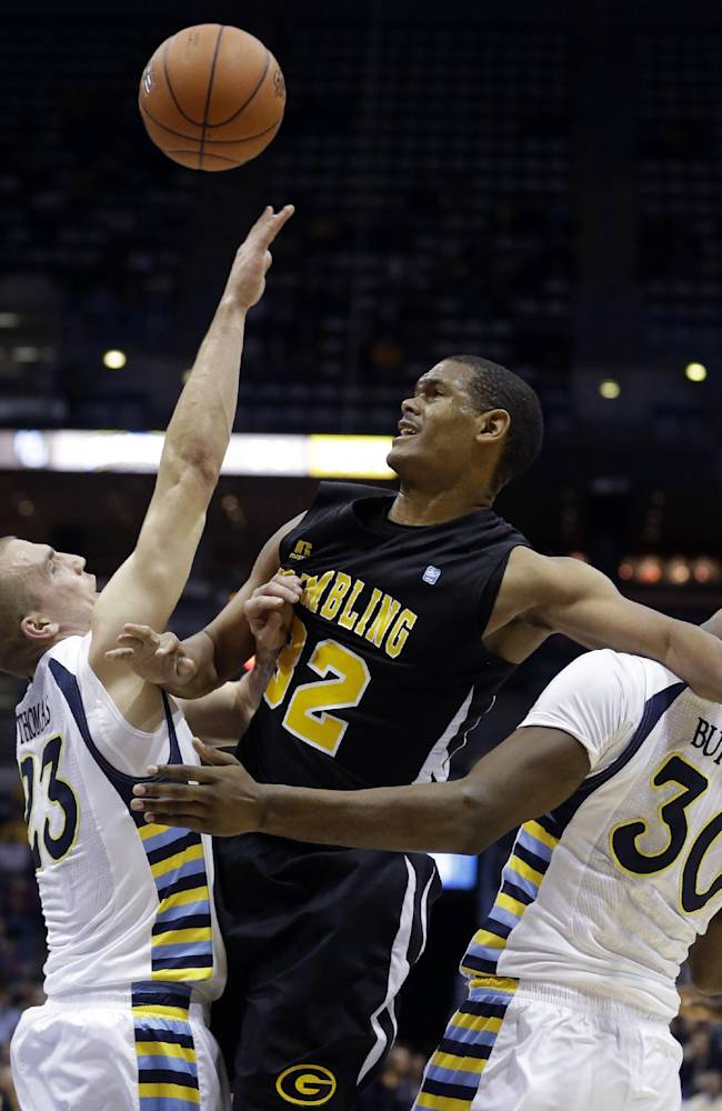 Grambling State's Chandler Thomas, center, is fouled as he tries to drive between Marquette's Jake Thomas (23) and Deonte Burton (30) during the second half of an NCAA college basketball game on Tuesday, Nov. 12, 2013, in Milwaukee