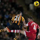 Hull City's Shane Long, left, jumps for the ball against Southampton's Morgan Schneiderlin during their English Premier League soccer match at the KC Stadium, Hull, England, Tuesday Feb. 11, 2014
