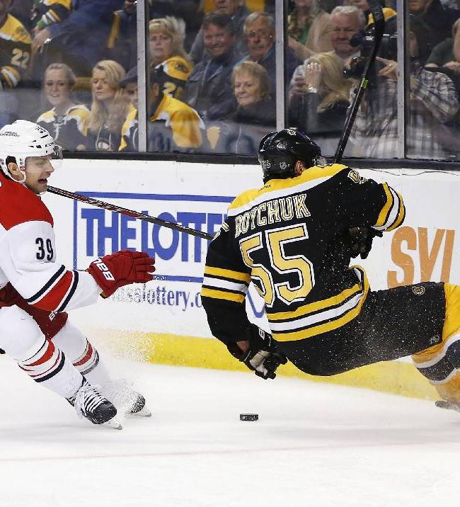 Boston Bruins' Johnny Boychuk (55) hits the boards while battling for the puck with Carolina Hurricanes' Patrick Dwyer (39) in the third period of an NHL hockey game in Boston, Saturday, March 15, 2014. Boychuk was injured on the play and left the ice. The Bruins won 5-1