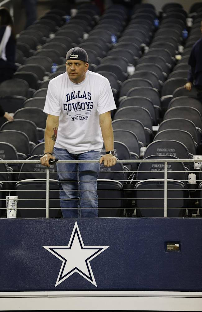 A Dallas Cowboys fan watches the field after a 23-22 loss at an NFL football game, Sunday, Dec. 29, 2013, in Arlington, Texas