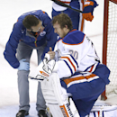 Edmonton Oilers goalie Ben Scrivens (30) is looked over by a trainer after he was hit by a San Jose Sharks stick during the third period of an NHL hockey game Tuesday, Dec. 9, 2014, in San Jose, Calif. San Jose won 5-2 The Associated Press