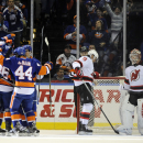 New York Islanders left wing Nikolay Kulemin (86) celebrates his goal with defenseman Calvin de Haan (44) and teammates as New Jersey Devils right wing Martin Havlat (9) and goalie Cory Schneider (35) react in the first period of an NHL hockey game at Nas