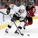 Pittsburgh Penguins center Sidney Crosby (87) skates with the puck as New Jersey Devils defenseman Andy Greene (6) skates behind him during the first period of an NHL hockey game, Friday, Jan. 30, 2015, in Newark, N.J. (AP Photo/Julio Cortez)