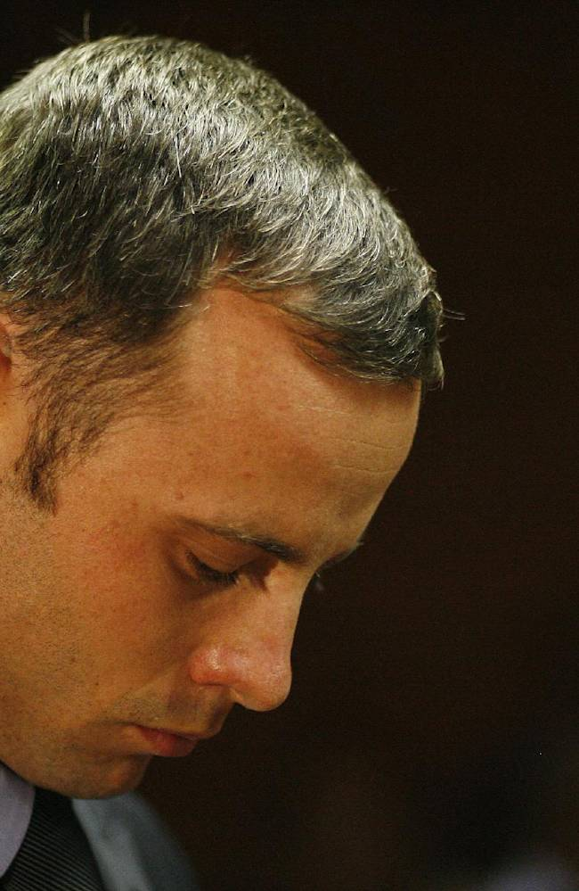 In this Feb. 21, 2013 file photo, Olympic athlete Oscar Pistorius stands during his bail hearing at the magistrate court in Pretoria, South Africa.Pistorius has been spending time with people who were close to the girlfriend he shot and killed on Valentine's Day, the Olympian's family said Thursday, April 11, 2013 in an indication that Pistorius is becoming more active while awaiting trial on a murder charge