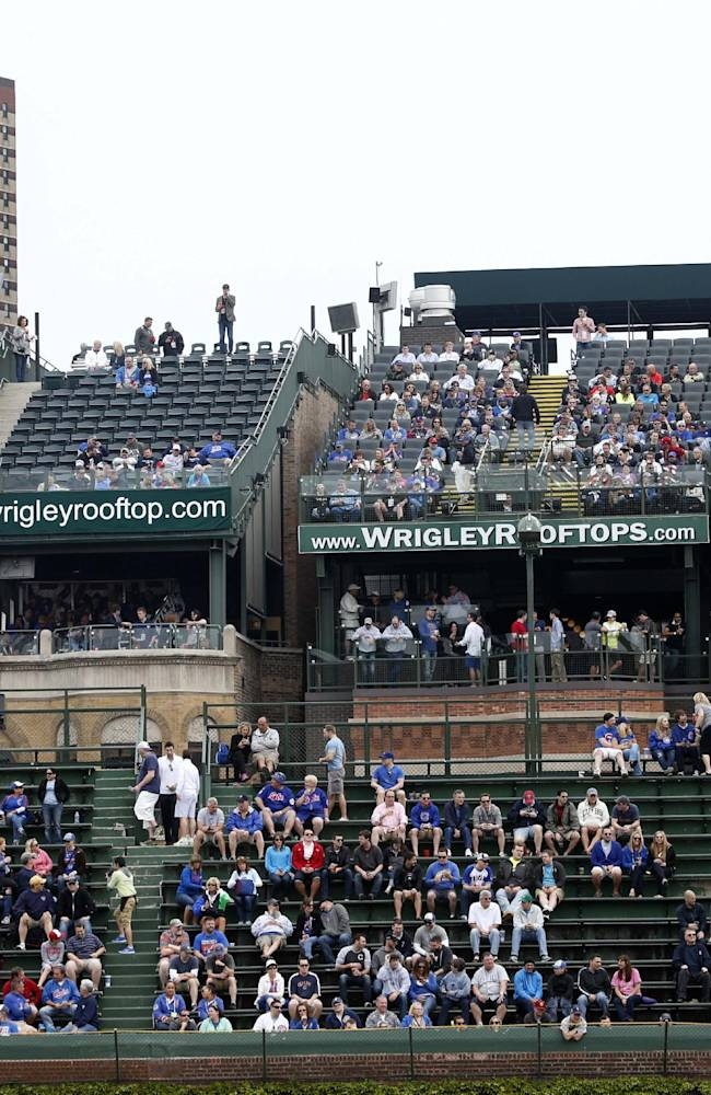 In this May 17, 2013, file photo, spectators watch a Chicago Cubs baseball game from several of the rooftop bleachers across the street from Wrigley Field in Chicago. The Cubs have asked the city's permission to put a 650-square-foot sign at Wrigley Field that may partially block views of the field from the surrounding rooftop businesses.  The club filed a permit application after talks with the rooftop owners fell apart last week.  The rooftop owners have said they will file a lawsuit if the team puts up anything that cuts into their views