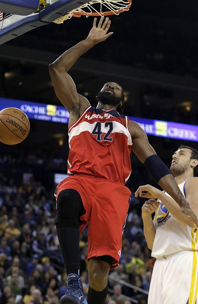Washington Wizards' Nene Hilario (42) scores over Golden State Warriors' Andrew Bogut, right, during the first half of an NBA basketball game, Tuesday, Jan. 28, 2014, in Oakland, Calif