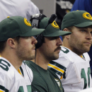 From left, Green Bay Packers' Scott Tolzien (16) sits with quarterback Aaron Rodgers, center, and Matt Flynn, right, on the bench during the second quarter of an NFL football game against the Detroit Lions at Ford Field in Detroit, Thursday, Nov. 28, 2013. (AP Photo/Duane Burleson)