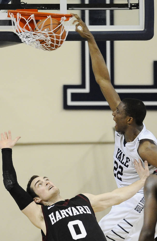 Yale's Justin Sears, right, dunks over Harvard's Laurent Rivard, left, during the second half of an NCAA college basketball game, Friday, March 7, 2014, in New Haven, Conn. Harvard won 70-58