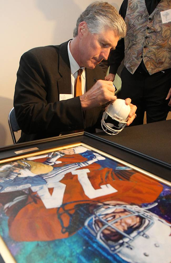 Former NFL star and Texas player Doug English signs a Texas Longhorn helmet before being inducted into the Texas Sports Hall Of Fame, Thursday, Feb. 27, 2014, in Waco, Texas