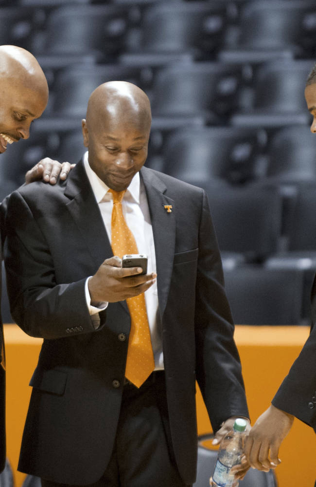 Tennessee men's coach Cuonzo Martin, left, gathers with Marco Harris, center, director of basketball operations, and Nicodemus Christopher, strength and conditioning coach, during the NCAA college basketball team's media day in Knoxville, Tenn., on Monday, Oct. 7, 2013