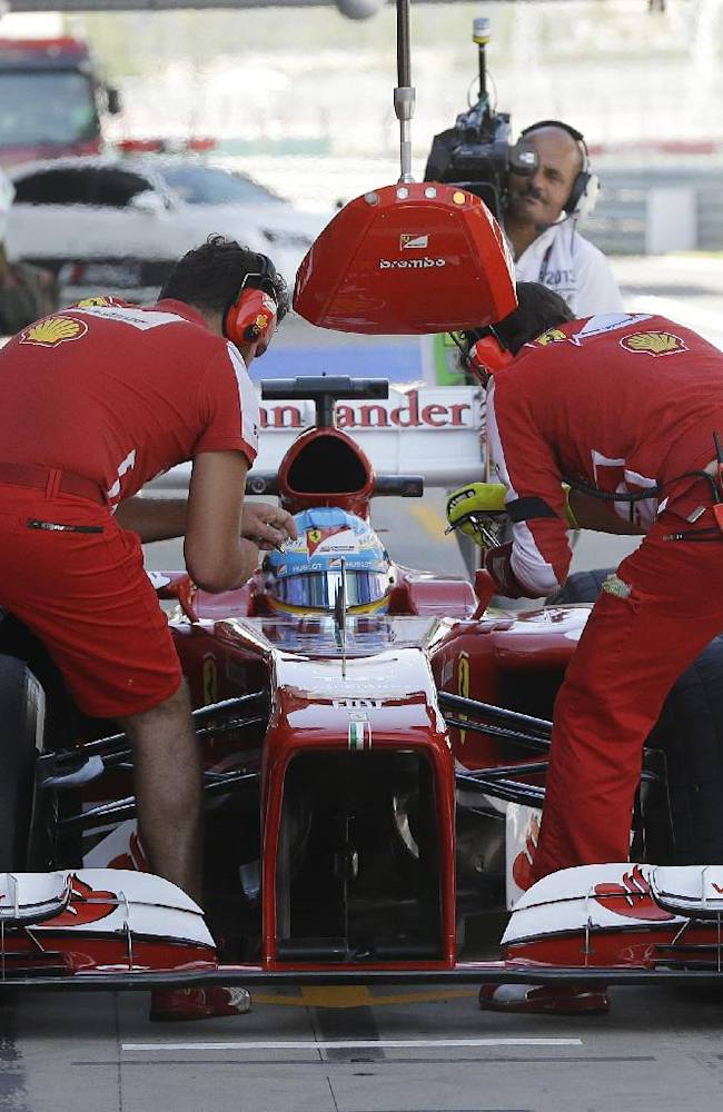 Ferrari driver Fernando Alonso of Spain waits in pit lane as his mechanics work on his car during the first practice session for the Korean Formula One Grand Prix at the Korean International Circuit in Yeongam, South Korea, Friday, Oct. 4, 2013