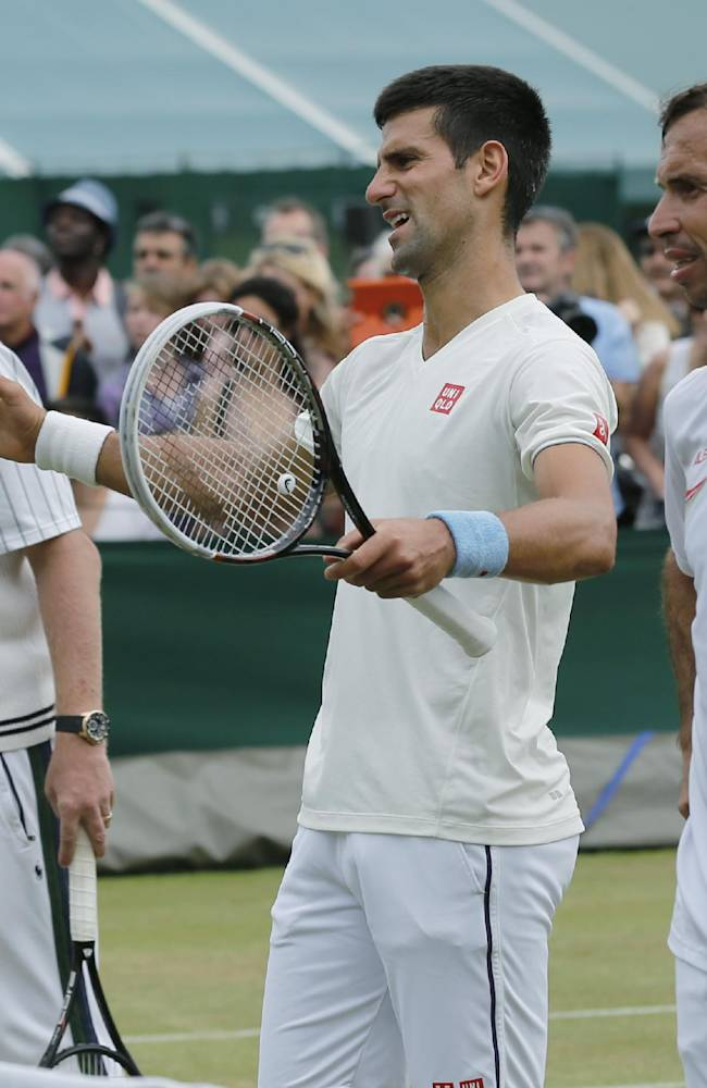 Novak Djokovic of Serbia, center, gestures as he stands between his coach Boris Becker, left, and Radek Stepanek of Czech Republic, right, during a training session at the All England Lawn Tennis Championships in Wimbledon, London, Saturday, July 5, 2014