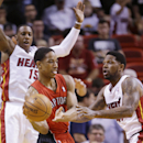 Toronto Raptors guard DeMar DeRozan passes past Miami Heat guard Mario Chalmers (15) and forward Udonis Haslem, right, during the first half of an NBA basketball game, Monday, March 31, 2014 in Miami The Associated Press