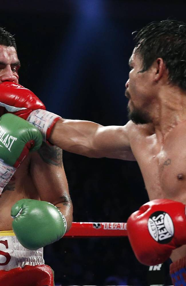 Manny Pacquiao, from the Philippines, right, lands a right to Brandon Rios of the United States during their WBO international welterweight title fight Sunday, Nov. 24, 2013, in Macau. Pacquiao defeated Rios by unanimous decision on Sunday to take the WBO international welterweight title and return to his accustomed winning ways after successive defeats