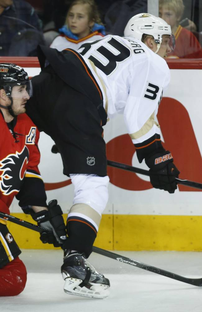 Anaheim Ducks' Jakob Silfverberg, right, from Sweden, crashes over Calgary Flames' Curtis Glencross during the second period of an NHL hockey game Wednesday, March 12, 2014, in Calgary, Alberta