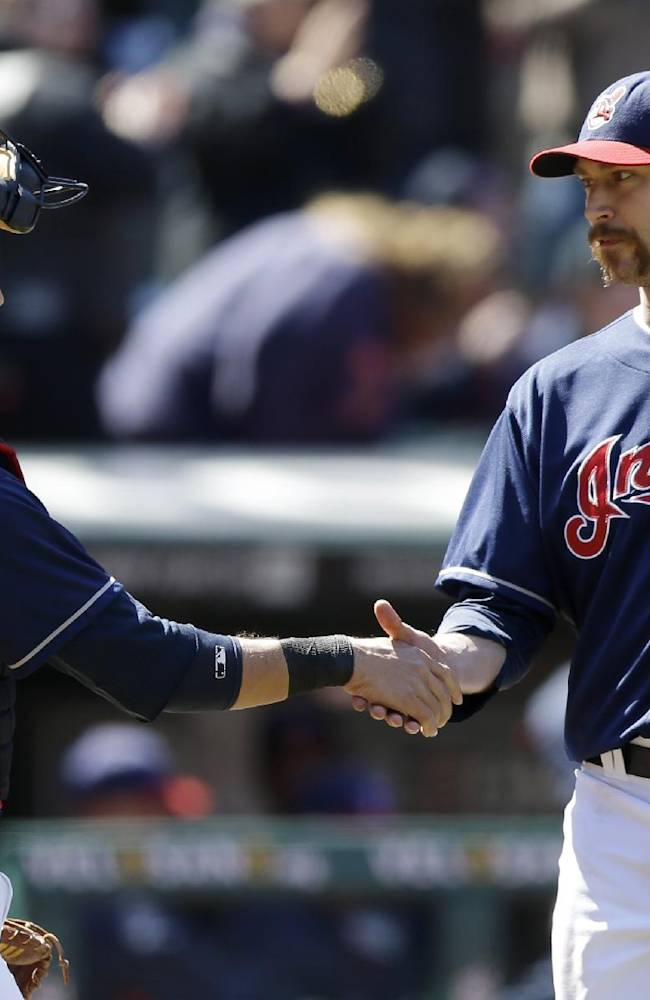 Cleveland Indians relief pitcher John Axford, right, is congratulated by catcher Yan Gomes after the Indians defeated the Padres 2-0 in the first baseball game of a doubleheader, Wednesday, April 9, 2014, in Cleveland
