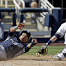 Milwaukee Brewers catcher Jonathan Lucroy can't handle the throw as San Diego Padres' Everth Cabrera scores from first on a single by Alexi Amarista during the second inning an exhibition baseball game Friday, March 7, 2014, in Phoenix The Associated Pres