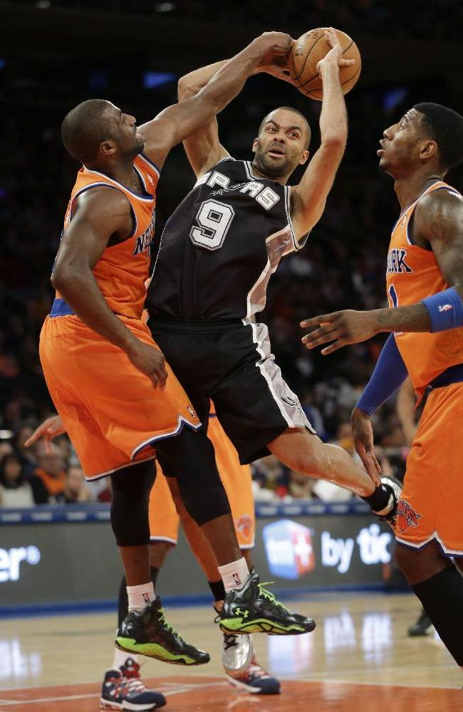 San Antonio Spurs' Tony Parker, center, passes around New York Knicks' defenders Raymond Felton, left, and Iman Shumpert during the first half of the NBA basketball game at Madison Square Garden Sunday, Nov. 10, 2013 in New York