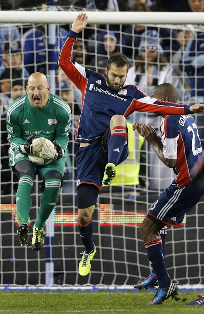 New England Revolution goalkeeper Matt Reis, left, makes a save next to New England Revolution defenders A.J. Soares, middle, and Jose Goncalves (23) during the second half of an MLS playoff soccer match against Sporting Kansas City in Kansas City, Kan., Wednesday, Nov. 6, 2013