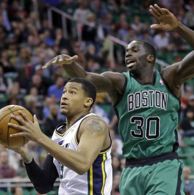 Utah Jazz's Trey Burke, left, goes to the basket as Boston Celtics' Brandon Bass (30) defends in the first quarter of an NBA basketball game, Monday, Feb. 24, 2014, in Salt Lake City