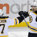 Boston Bruins' Patrice Bergeron (37) celebrates an overtime goal by teammate Brad Marchand (63) during an NHL hockey game against the Buffalo Sabres Thursday, Oct., 30, 2014, in Buffalo , N.Y. Boston won 3-2. (AP Photo/Gary Wiepert)