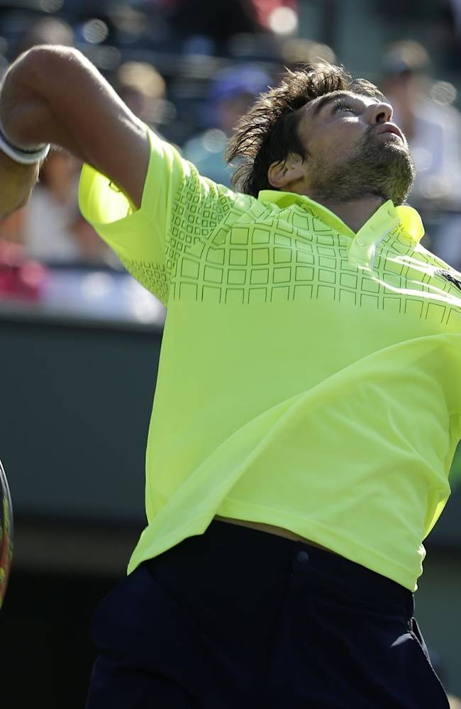 Jeremy Chardy, of France, prepares to hit an overhead smash to Novak Djokovic, of Serbia, at the Sony Open tennis tournament, Friday, March 21, 2014, in Key Biscayne, Fla
