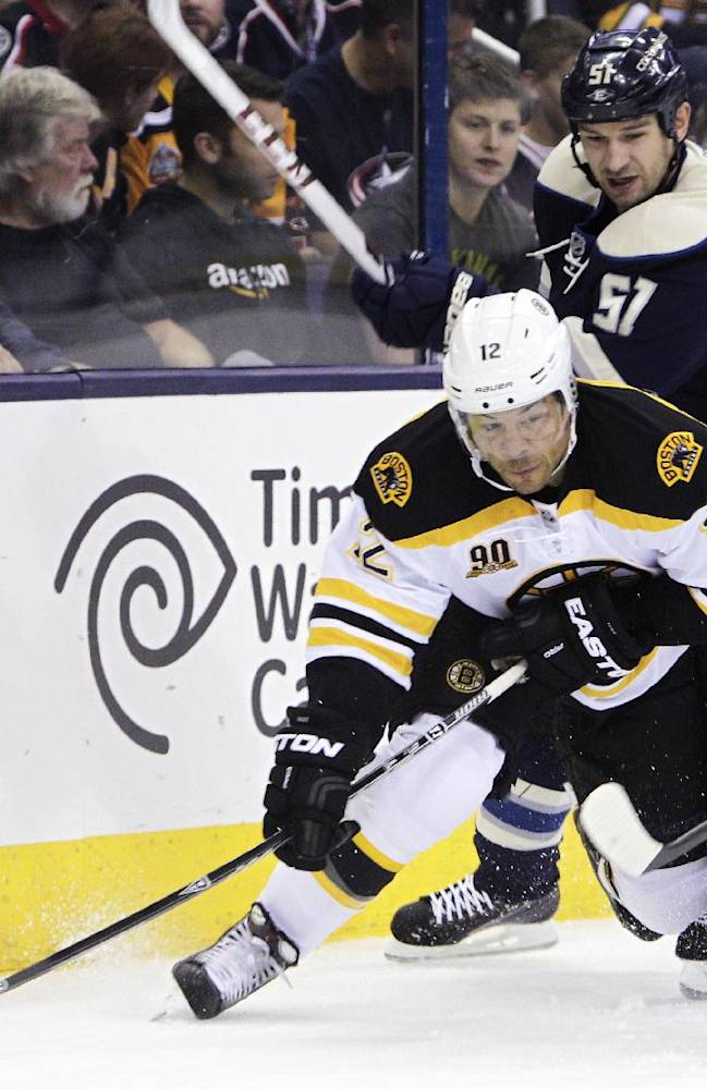 Boston Bruins' Jarome Iginla, left, tries to pass the puck as Columbus Blue Jackets' Fedor Tyutin, of Russia, defends during the first period of an NHL hockey game Saturday, Oct. 12, 2013, in Columbus, Ohio