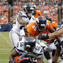 Denver Broncos running back Ronnie Hillman (23) scores a touchdown as Seattle Seahawks defensive end Cliff Avril (56) defends during the first half of an NFL preseason football game, Thursday, Aug. 7, 2014, in Denver The Associated Press