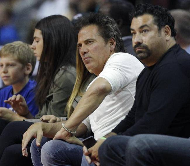 Detroit Pistons owner Tom Gores, second from right, watches his team take on the Miami Heat in the first half of an NBA basketball preseason game on Thursday, Oct. 10, 2013, in Detroit
