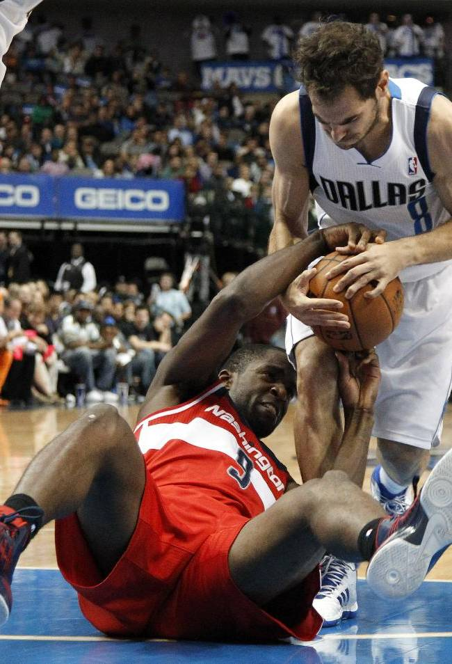 Dallas Mavericks' Jose Calderon wins a defensive rebound against Washington Wizards' Martell Webster (9) after a scramble on the court in the first half of an NBA basketball game, Tuesday, Nov. 12, 2013, in Dallas
