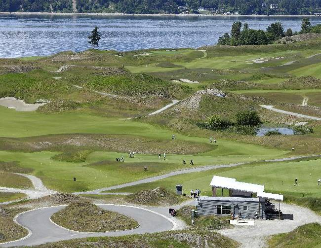 In this May 20, 2014 photo, the Chambers Bay Golf Course, including the signature lone tree, is seen from the clubhouse in University Place, Wash. The links style course will host the 2015 U.S. Open