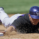 Colorado Rockies' Drew Stubbs dives back to first base during the third inning of a spring exhibition baseball game against the San Diego Padres, Monday, March 17, 2014, in Peoria, Ariz The Associated Press