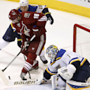 St. Louis Blues' Brian Elliott (1) makes a save on a shot by Arizona Coyotes' Shane Doan, middle, as Blues' Jay Bouwmeester defends during the third period of an NHL hockey game Tuesday, Jan. 6, 2015, in Glendale, Ariz. The Blues defeated the Coyotes 6-0