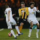 Manchester United's Phil Jones, left challenges Cambridge United's Liam Hughes, centre as Manchester United's Marouane Fellaini turns away during their English FA Cup fourth round soccer match between Cambridge United and Manchester United, in Cambridge,
