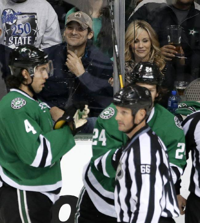 Dallas Cowboys quarterback Tony Romo, center with ball cap and his wife Candice, right, watch during a break from play in the third period of an NHL hockey game between the Minnesota Wild and Dallas Stars, Tuesday, Jan. 21, 2014, in Dallas. The Stars won 4-0