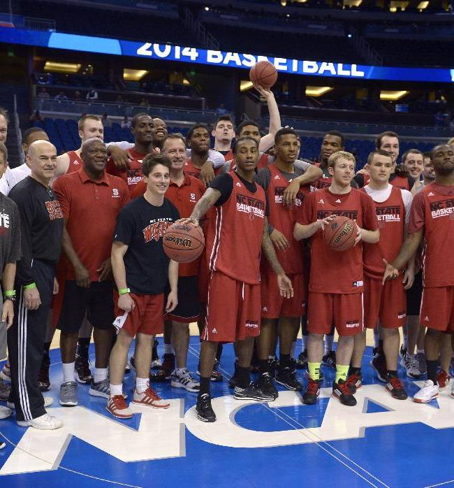 North Carolina State players and staff pose for a group photo at the middle of the court during a practice for an NCAA men's college basketball tournament game in Orlando, Fla., Wednesday, March 19, 2014. North Carolina State will face Saint Louis in the second round of the tournament on Thursday