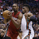 Miami Heat's Chris Bosh, left, drives against Milwaukee Bucks' Jeff Adrien during the first half of an NBA basketball game Saturday, March 29, 2014, in Milwaukee The Associated Press